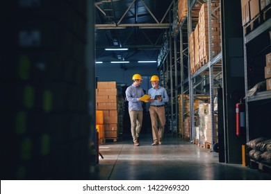 Two business partners in formal wear and with protective yellow helmets on heads walking and talking about business. Younger one holding folder with data while older one using tablet. - Shutterstock ID 1422969320