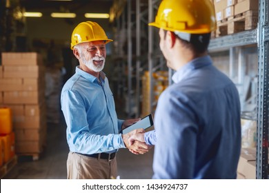 Two business partners in formal wear and with helmets on heads shaking hands in warehouse. Senior adult businessman holding tablet.