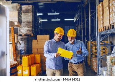Two business partners in formal wear and with protective yellow helmets on heads standing in warehouse and comparing data. Younger one pointing at document in folder while older one holding tablet.