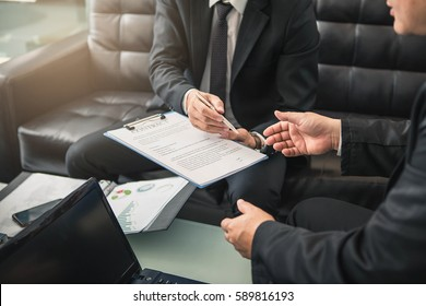 Two business partners signing a document. Businessman sitting at office desk signing a contract .
