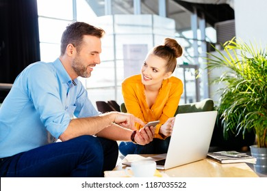 Two business partners smiling talking about work with smartphone and laptop