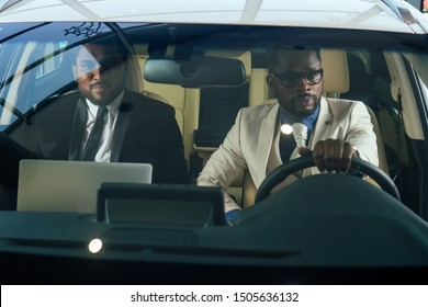 two business partners working together in front seat of car at evening dark time .