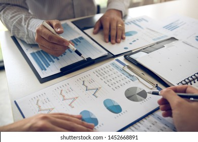 Two business partnership coworkers analysis cost work progress and gesturing with discussing a financial planning graph and company financial during a budget meeting in office room.