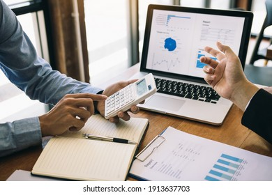 Two business partnership coworkers analysis strategy with discussing a financial planning graph and company budget during a budget meeting in office room.