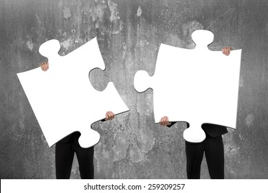 Two business people assembling blank white jigsaw puzzles with concrete wall background