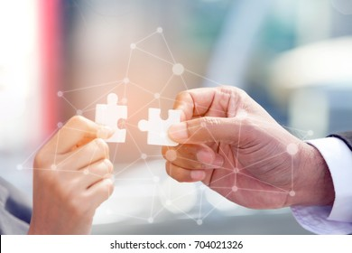 two business people assembling jigsaw puzzle and represent team support and in office with digital layer business strategy and social media diagram,partnership sales team collaborate with competitors