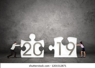 Two business people assembling number 2019 on two puzzle pieces. Shot with concrete background