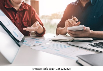 Two business people are calculating earnings financial costs of the company on desk at the office room.