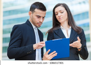 Two business people discussing about some documents