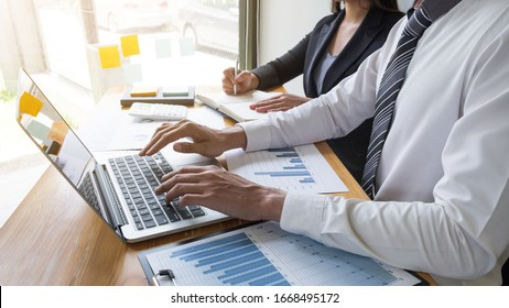 Two business people are discussing about business graph on the table in the office room. business discussing and planning strategy, concept.
