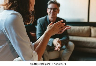 Two business people discussing in office lounge. Businesswoman talking with a male colleague in office lobby. - Shutterstock ID 1702602871