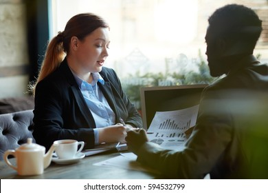 Two business people during work meeting in modern cafe: Young professional woman explaining statistics data to African American partner looking at documents with graphs and charts