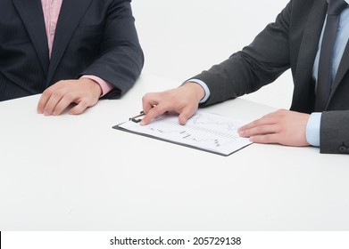 Two business people in elegant suits working in team together with documents, holding clipboard with papers isolated on white background