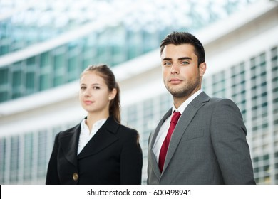 Two business people in front of their office