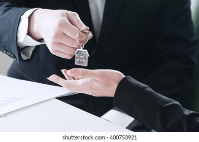 Two business people handing over the keys after a successful deal