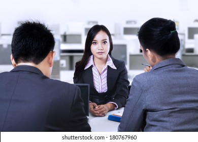 Two business people having a interview with job applicant