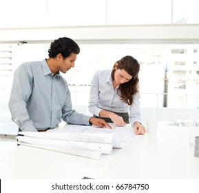 Two business people looking at a new project standing at a table