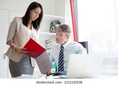 Two business people looking a red file in a small office in a real life business