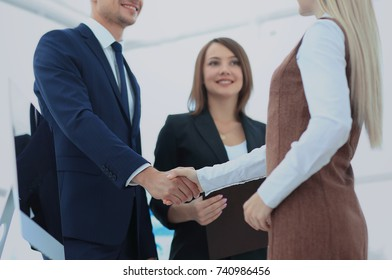 Two business people making agreement, their female colleague sta