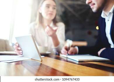Two business people, man and woman, sitting at desk and discusing data on tablet computer; low angle view