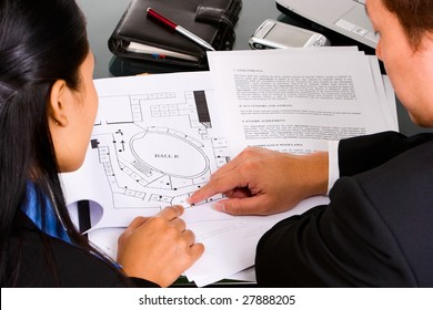 Two business people, man and woman discuss about their property planning.