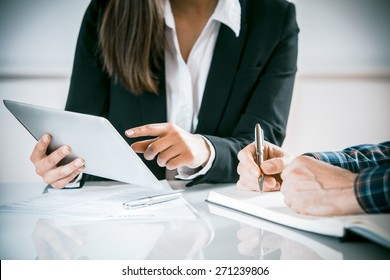 Two business people in a meeting discussing information on a tablet-pc and taking notes as they work together as a team, close up view of their hands seated at a desk