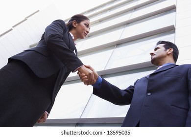 Two business people shaking hands outside modern office