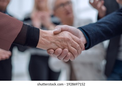 Two business people shaking hands in front of their colleagues