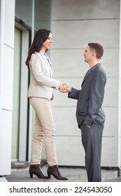 Two business people shaking hands in front of office building