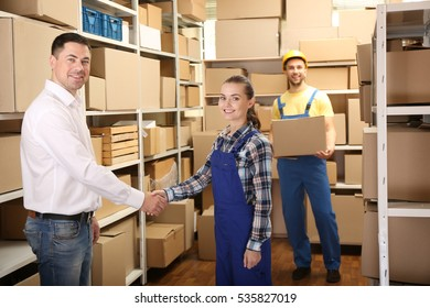 Two business people shaking hands at warehouse