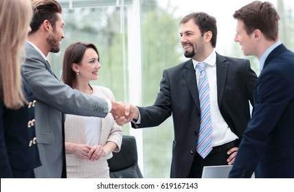 Two business people shaking hands at the business meeting with t