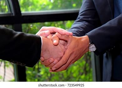 Two business people shaking hands in dark tone , people shaking hands after finishing meeting, Business handshake