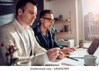 Two business people sitting at the desk by the window and working together in the office