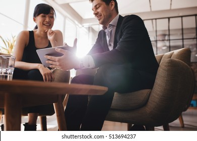 Two business people sitting at lobby and discussing project on digital tablet. Young businesswoman and businessman looking at tablet computer and smiling.