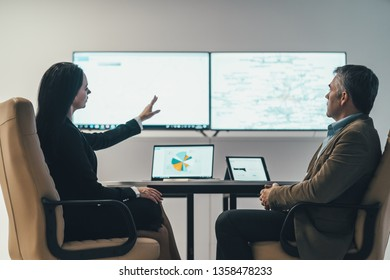 The two business people sitting at the table near a screen