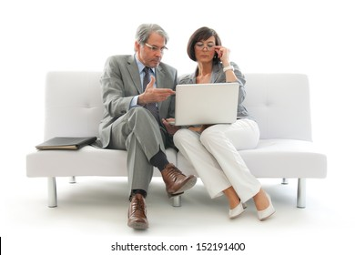 Two business people sitting and working together on a white sofa