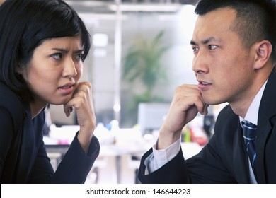 Two Business people staring at each other across a table