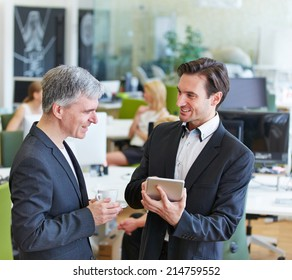 Two business people with tablet computer talking in the office