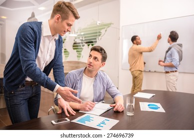 Two business people are talking sitting at the table on background of colleagues.