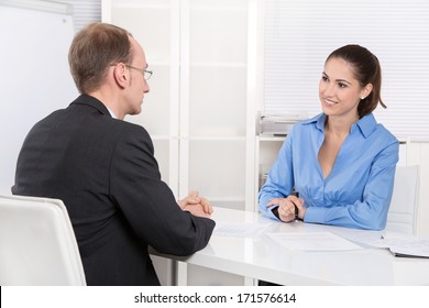 Two business people talking together at desk - adviser and customer