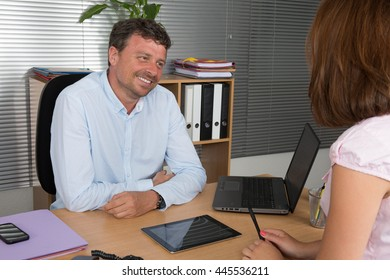 Two business people talking together at the desk - adviser and customer