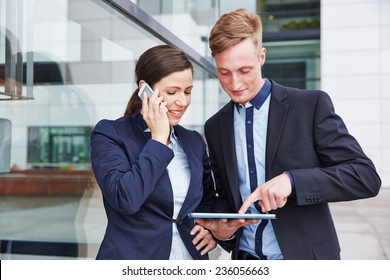 Two business people using smartphone and tablet computer in the vcity