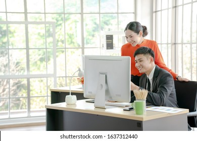 Two business people are working from modern office analyzing market research statistics both using printed media and computers.
