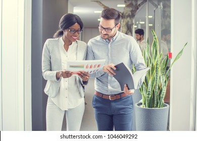 Two business people working together with documents while having informal meeting in office hallway.