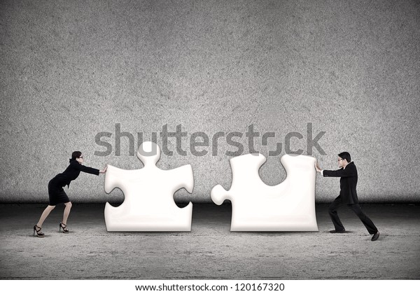Two business people are working together to put two puzzles in order to succeed