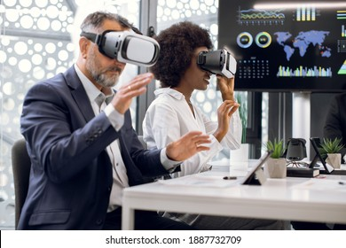 Two business persons, mature Caucasian man and young African woman, wearing vr goggles, developing a project or testing new mobile applications, while sitting at the meering in office - Shutterstock ID 1887732709