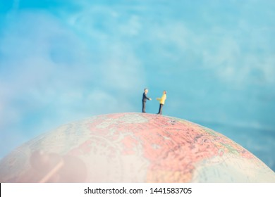 Two business professionals shaking hands on the top of the world. Globalism or international merger deal. Travel for work. Connections between different nationalities and cultures.