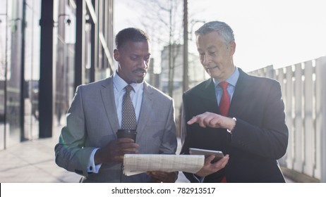 Two business professionals walking and discussing news