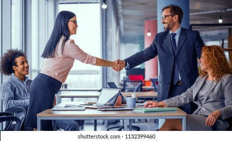Two business teams successfully negotiating, shaking hands. At meeting table business groups shaking hands on completed deal. Man and woman handshake. Toned concept.