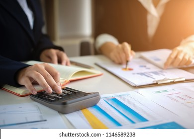 Two Business woman or Accountant working with calculator for investigation of corruption account. Anti Bribery concept.
